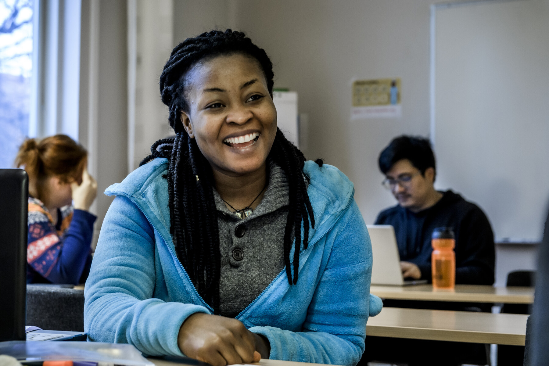 A woman student looking happy in a classroom. Photo.
