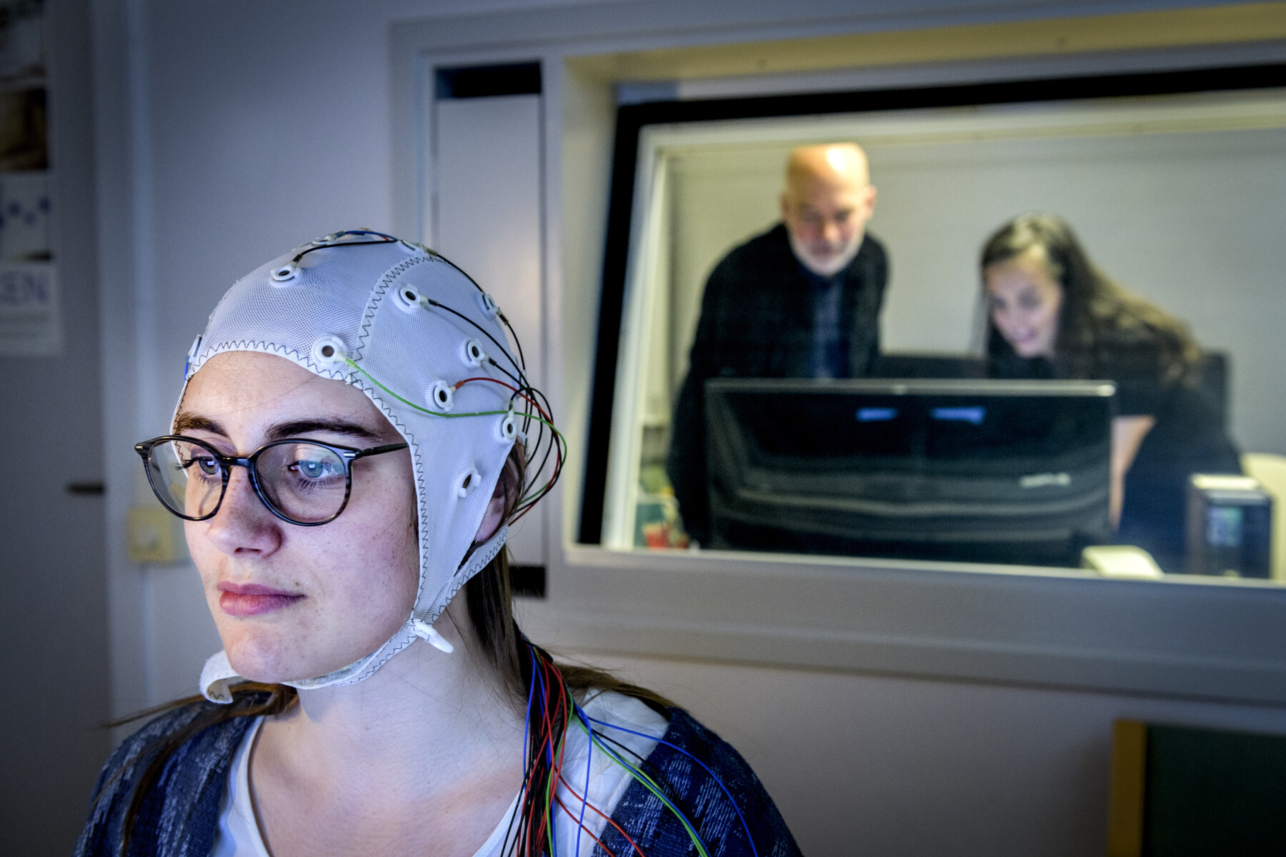 A person taking part in a brain activity study. The person wears a cap connected by wires to a computer.