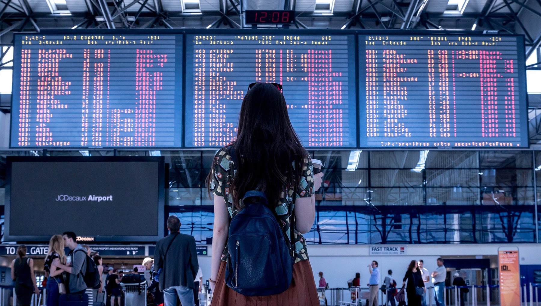 A woman at an airport, looking at the departure flights screen. Photo.